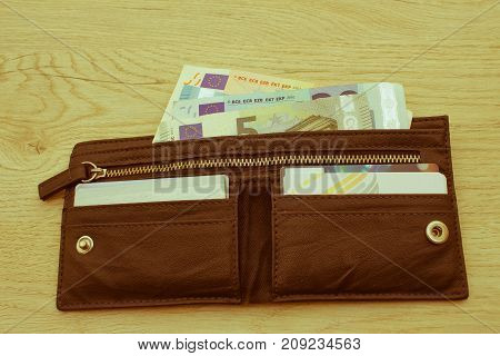 men's black wallet money in cash wooden background. money bank notes inserted in the leather wallet - Retro color