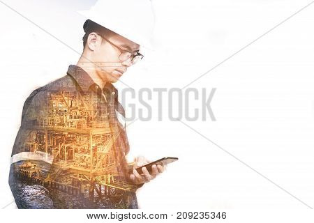 Double exposure of Engineer or Technician man with safety helmet using smart phone with offshore exploration and production platform background for oil and gas business concept.