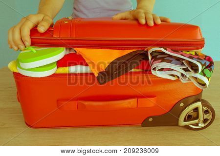 Young woman hands packing suitcase. Travel and vacations concept. Women's clothes and accessories in red suitcase things prepared for travel - Retro color