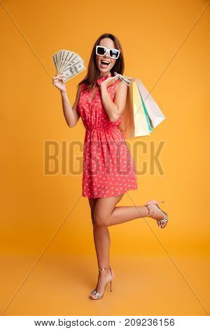 Full-length photo of happy exited young woman in red dress holding credit card and  shopping bags, looking at camera, isolated on yellow background