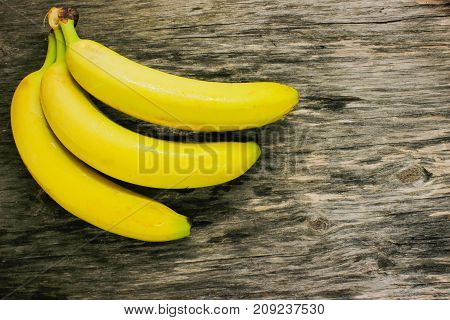 Sweet bananas on a gray wooden table. View from above