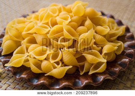 Pasta made from flour scattered on a plate on a table.