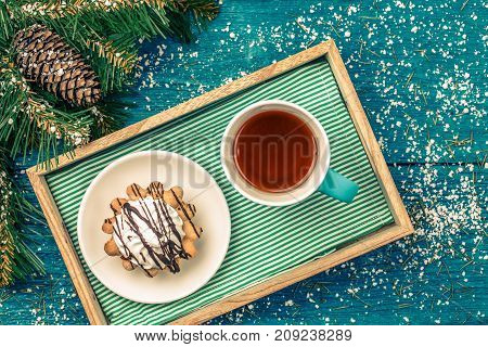 New Year's photo of tea with cake on table with spruce branch