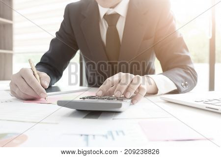 Finance conceptfinance control audit man calculate business financial data on calculator.