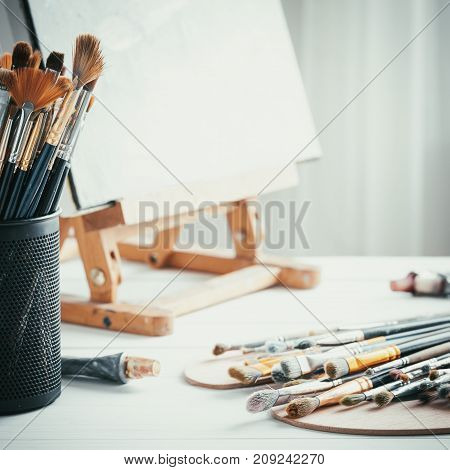 Artistic Equipment In Painter Studio: Easel, Paint Brushes, Tubes Of Paint, Palette And Paintings On