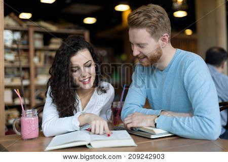 Young attractive students spending time in coffee shop reading books