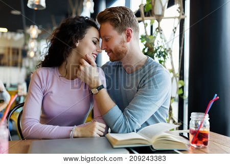 Young happy couple on date in coffee shop having romantic times