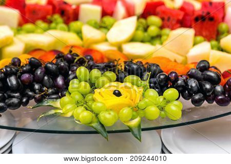 Fruits on plate on wooden surface. Bananas, apples , pineapple, oranges. Assorted fruits on the plate. Flat lay. Vegan. Healthy food concept.