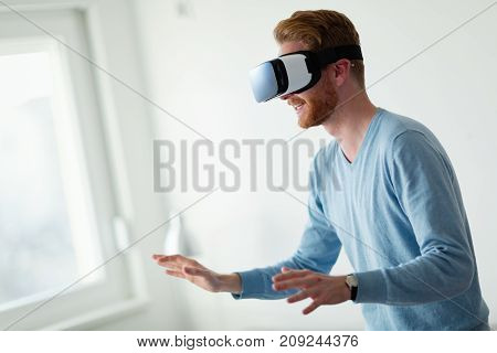Man wearing virtual reality headset at home trying new experience