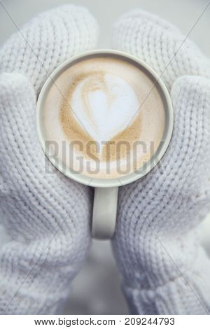 coffee cappuccino mug in hands mittens outdoor in the winter on Christmas Eve