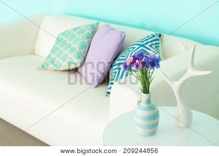 Lilac accent in modern interior. Table with cornflowers and comfortable couch in living room
