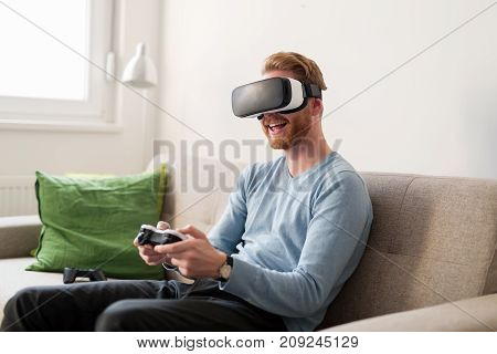 Handsome young man playing video games with virtual reality headset
