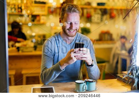 Cheerful handsome man using mobile phone in coffee shop
