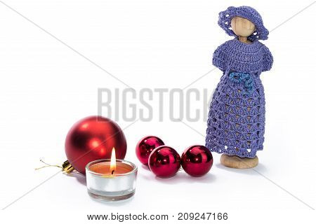 Christmas doll figures with candle and red balls against white background