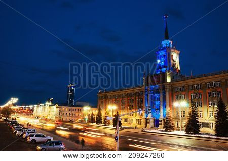 Yekaterinburg Russia. Illuminated administration building in Yekaterinburg Russia at night. Dark blue sky and car traffic lights