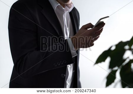 Mobile security, phisning and online crime. Businessman or man in a suit holding a smartphone in dark shadow. Financial fraud with smart device.