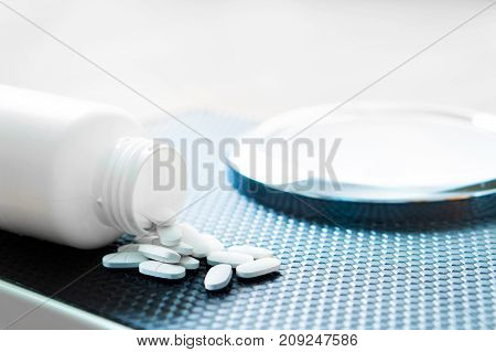 Weight loss pills on a scale. Diet medicine spilled out from bottle.