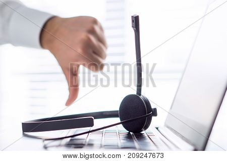 Unhappy help desk, support hotline or call center person showing thumbs down. Tele marketing professional having horrible day, not satisfied. Bad feedback or working conditions.