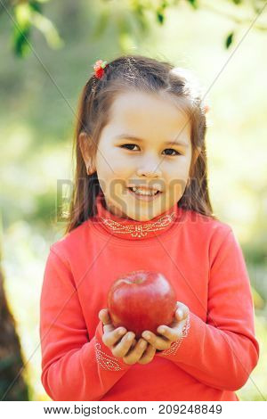 A little girl in red golf is holding a red apple
