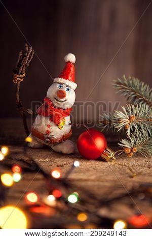 Christmas snowman decoration against the backdrop illumination and fir tree.