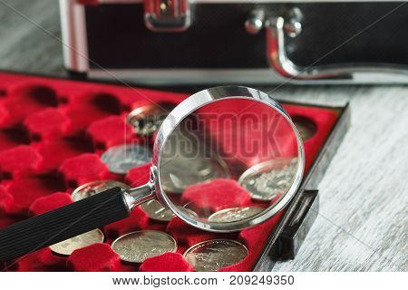 Different Collector's Coins In The Box For Coins And A Magnifying Glass