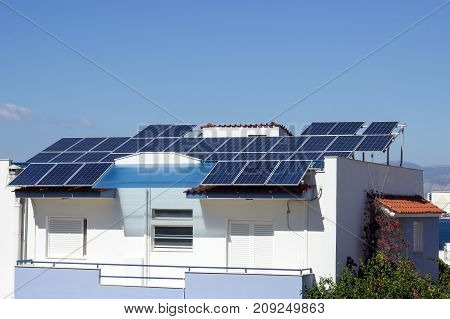 Roof with solar panels fragment under sunny blue sky. Greece.
