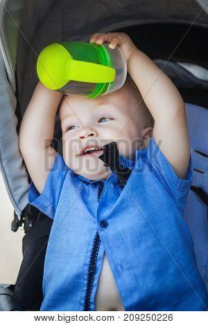 cheerful boy blonde boy sitting in pram, fun child playing with his cup in pram