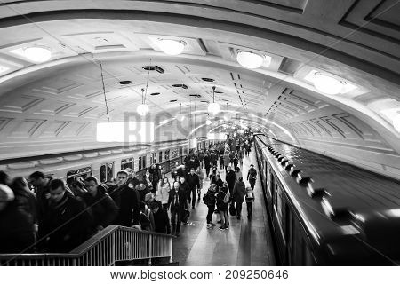 MOSCOW RUSSIA - OCTOBER 23 2016: Inside a Lenin Library metro station at rush hour in Moscow Russia. Unidentified people at the platform with moving trains. Black and white