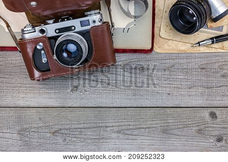 Old Still Camera In Leather Case, Photo Album And Old Pictures On Wooden Desk