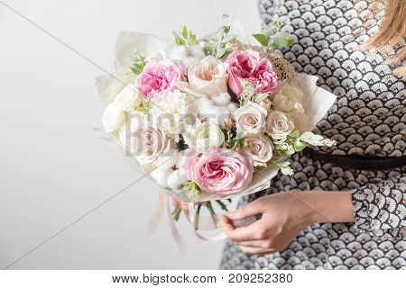 Mix flowers. Luxury bouquets in the girl's hands. on a light gray wall
