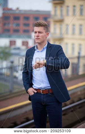blond man checking the time and waiting for the train