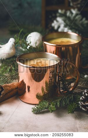 Traditional winter eggnog in copper mugs with milk, rum and cinnamon, sprinkle with grated nutmeg, christmas decorations