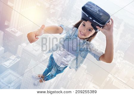 Content with result. The top view of a charming little girl showing thumbs up and removing VR headset after the game while her image being superimposed on an urban background