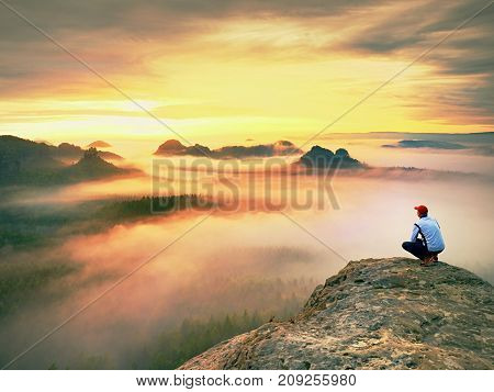 Tired  Backpacker Watch Spring Daybreak In Rocky Mountains. Hiker In Baseball Cap And White Shirt.