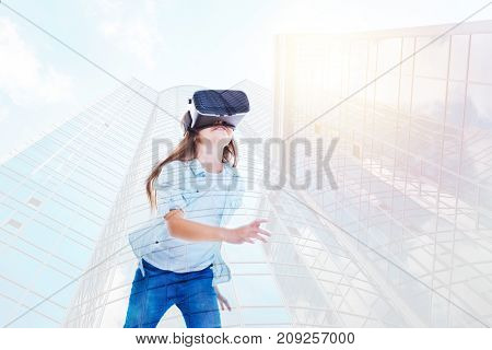 Energetic video game. Cute little girl wearing a VR headset, playing a video game and running while having the image of skyscrapers as her background