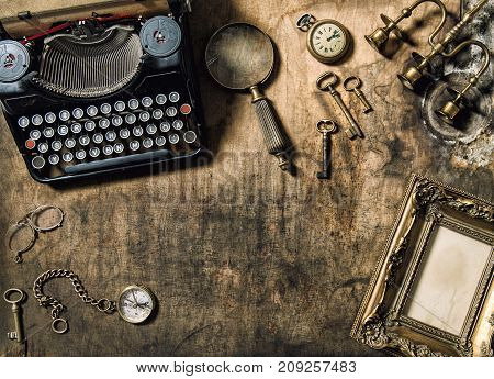 Vintage typewriter golden frame old office accessories on wooden table. Nostalgic still life