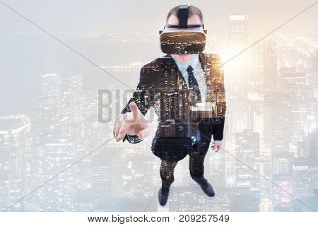 First experience ever. Neat young man in a business suit wearing a VR headset and pointing with his finger while his image being superimposed on the night city landscape