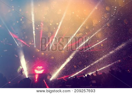 People enjoying a summer music festival. Falling of colorful confetti