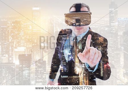 Futuristic equipment. Charming elegant young man in business suit wearing a VR headset and pointing with his finger as if being about to touch something