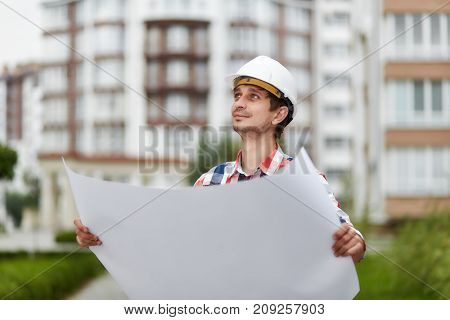 Young male constructionist smiling looking away holding blueprint of a building under construction future development real estate business industry businessman concept