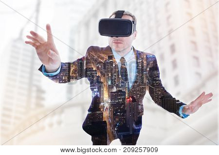 Refreshing experience. Handsome young businessman in a suit wearing a VR headset and trying out a new VR headset while having a night city view superimposed on his suit