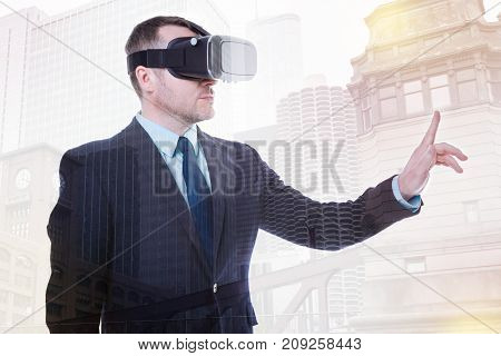 Interaction with technologies. Handsome young man in a business suit standing half-turned, wearing a VR headset and raising his index finger as if being ready to touch a screen