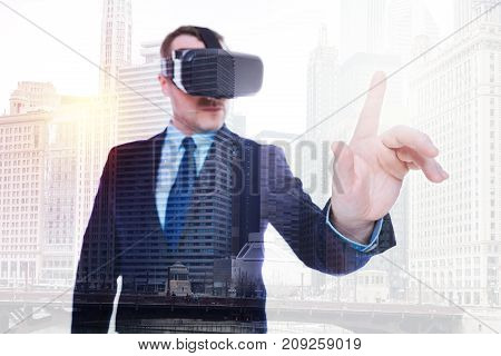 Experienced user. Young bristled businessman in a suit wearing a VR headset and raising his index finger as if being about to touch something while standing against urban background