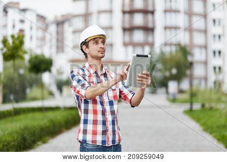 Professional male constructionist looking around using digital tablet standing outdoors near living houses technology connection mobility wireless 4G 3G inspection project profession concept