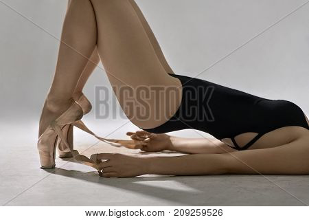 Young ballerina in a black leotard lies on the floor on the gray background in the studio. She holds her pelvis in the air while leans on the arms and toes. Girl holds ribbons of her pointe shoes.