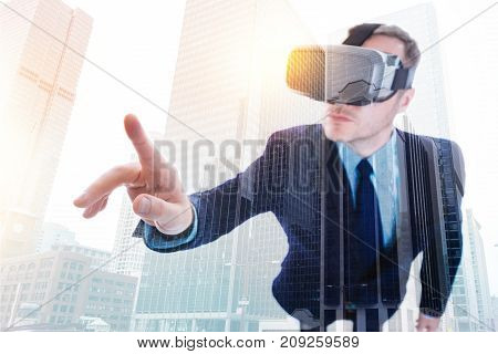 Breaking reality borders. Handsome young man in a business suit testing VR headset and raising his finger, being ready to touch some object in virtual reality with his finger