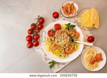Overhead Of Dinner Table. Pasta Tagliatelle With Grilled Shrimps, Salmon Fish, Gouda Cheese, Serving