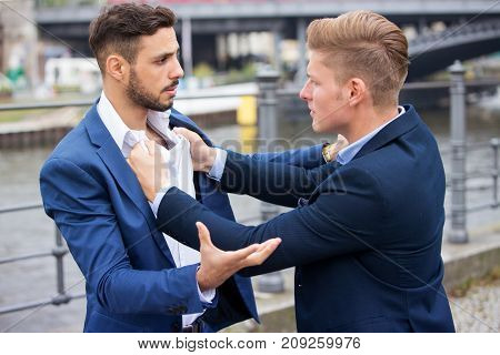 two young businessmen having a fight outside