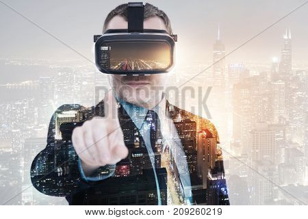 Night in bustling city. Handsome young man pointing at the camera with an index finger while wearing a VR headset and having his image superimposed on the night city background