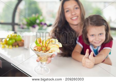 Cute little girl cooking with her mother. Healthy food, cooking healthy salad with fruits ingredients. Mom and daughter cooking together. Child shows thumbs up.